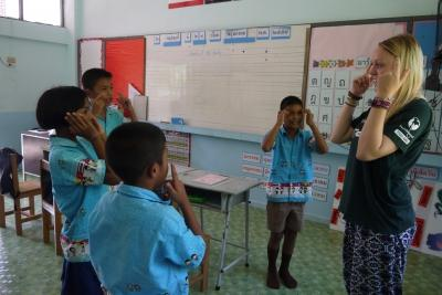 A Projects Abroad volunteer teaches her students head shoulders knees and toes when she volunteers as an English teacher in Thailand.